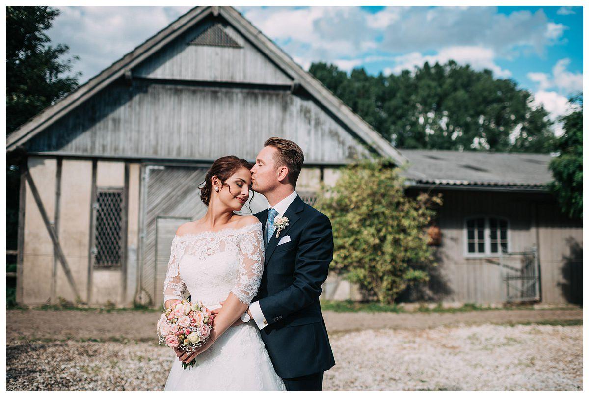 Bräutigam küsst Braut auf Gut Schwarzenbruch
