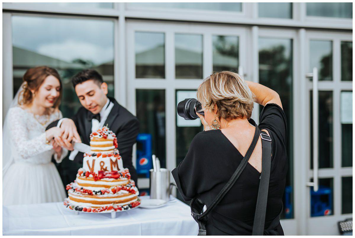 Brautpaar wird beim Kuchen anschneiden fotografiert